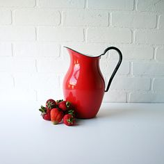 red enamelware pitcher with black trim