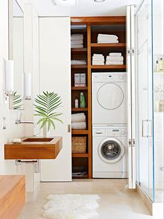 Stacked washer and dryer with shelving in a hall closet.