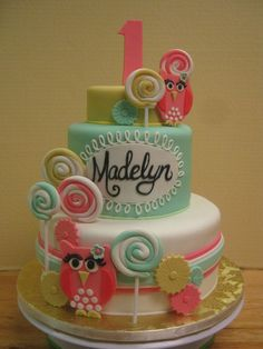 First birthday tiered owl and lollipop cake in gold, pink and mint green.