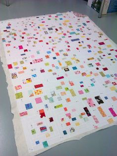 confetti quilt - try a version of this using white jelly roll, randomly cut and sewn back with scraps then do the Jelly Roll Race assembly... It might be close to this.