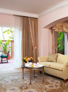 Rooms feature the hotel's signature pink with white detailing.