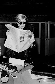 Andy Warhol reads the paper.