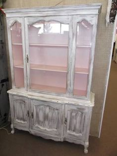 SOLD - Charming shabby chic china hutch - heavily distressed exterior with light pink interior. 3 door cabinet in base for hidden storage - glass door and side panels on top - 1 piece construction. ***** In Booth A8 at Main Street Antique Mall 7260 E Main St (east of Power RD on MAIN STREET) Mesa Az 85207 **** Open 7 days a week 10:00AM-5:30PM **** Call for more information 480 924 1122 **** We Accept cash, debit, VISA, MasterCard or Discover.