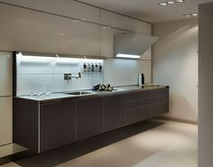 Wall hung bulthaup b3 kitchen area featuring glass panelling and a built in organisational system.