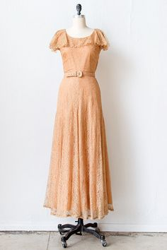 1940s Dubarry peach lace gown. This dress features a sleeveless bodice with a ruffle layer at the neckline that creates the look of a short fluttler sleeve. The dress is fitted from the bodice to about the hips where the skirt flares slightly from the body. At the waist it has a matching belt. There is a side zipper closure.