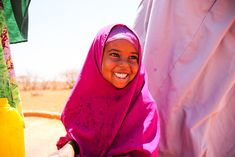 Photo Essay: The Bright Colors of Somaliland. Namacima poses next to a World Concern-rehabilitated berkad (a local water collection system). Only one in three people in the region have access to safe drinking water #water #photoessay #Africa #Somaliland