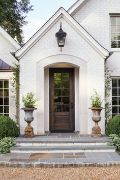Gable, arched opening, large lantern light outside, tall entry door, 2 planter urns, white brick