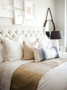 Tufted cream linen headboard with nice mix of textures & pillow shapes/sizes