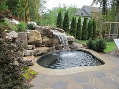 A custom made inground spa with a natural boulder waterfall, surrounded by a Mega Arbel Belgard paver patio.