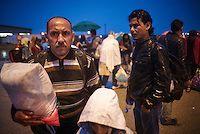 Budapest le 4 et 5 septembre 2015, en prenant le bus pour l'Autriche nous amenant sans un camp de réfugiés à Nickelsdorf à la frontière Austro Hongroise, avec des immigrés Afghans Zabihullah Sharifi 28 ans avec sa femme Bushre 24 ans et leur fille d'une année Behsa, dans des conditions extrêmement difficile au lever du jour sous la pluie les autorités autrichiennes les ont pris en charges avec 2000 migrant venant des pays du moyen orient, tous partis de la gare de Keleti de Budapest. ©… Bus, Afghans, Budapest, 28 Years Old, Middle East, In The Rain, Austria, Train Station, September