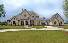 This luxury chateau mansion house plan offers varied ceiling treatments. The elegant two-story foyer includes a winding staircase to the second story, plus a wine bar, and a barrel vault ceiling.