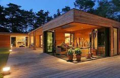 GLASS AND WOOD ATRIUM HOME DESIGN SURROUNDED BY YOUNG PINES OF FOREST