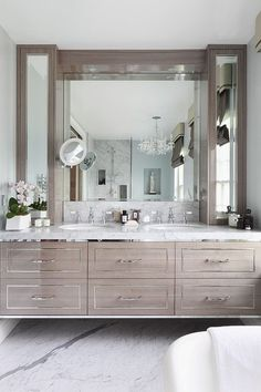 Floating gray washed wood vanity with metallic trim detail | Family Residence by Oliver Burns