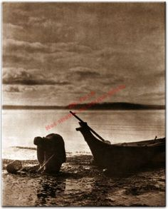 1913 photo of a Coast Salish or Chinook Indian woman with her canoe and clam digging basket. Native American Oregon and Washington