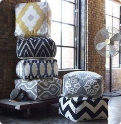 Floor Poufs to move around and gather around - West Elm $249 (nicely portrayed next to the exposed brick wall)