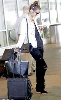 Alessandra Ambrosio leaned on her bags at the airport, wearing ripped black jeans, a black T-shirt, a white leather biker style jacket and platform sneakers