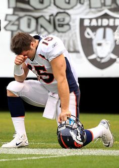 Tim Tebow Photos - Tim Tebow  15 of the Denver Broncos kneels on the ground b555289a8