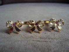 Anel duplo em metal dourado, com formato de lacinhos, e aplicação de strass Swarovski nas cores cinza e rosa R$29,90