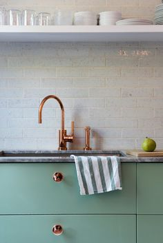 Lyons and Brill designed several custom touches, like the copper-plated knobs they installed on the Sektion kitchen cabinetry from IKEA, painted in Farrow & Ball's muted Breakfast Room Green.