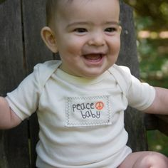 Peace Baby...  what we all want is a little more peace in the world...so we can start with Peace Babies..    Our very popular design is on our  100% certified organic cotton infant lap tee or one piece with organic cotton patch.    Color: Natural with brown and orange embroidery    Made in USA    Care: Machine wash cold, mild detergent, dry low heat. Iron on reverse side or between 2 pieces of cloth if necessary.    Not intended for sleepwear