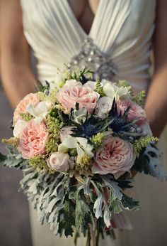 Beautiful bridal bouquet of coral garden roses with cream astibile, super bombastic roses, freshia, dusty miller and thistles.