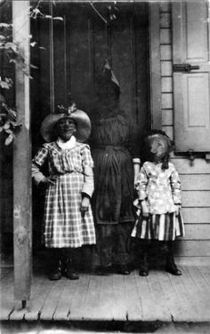 Turn of the Century Halloween Photo. The person in the middle seems to be materializing through the door, although it's probably faded or not developed properly, etc. ; )