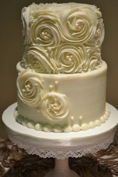 buttercream wedding cake with rosettes and pearls.  This is my first choice but with the cake resting on a wood round.