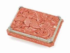 A FRENCH 18K GOLD AND DIAMOND MOUNTED CORAL POWDER CASE BY BERLIOZ-LEROY, PARIS, CIRCA 1920; THE CORAL QING DYNASTY. The rectangular hinged box and cover with top and bottom panels carved in openwork with a bird amidst lotus flowers and vines, surrounded by a fine border of diamonds, the box opening reveal a fitted mirror and compartment.