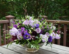 Large table flower centerpiece with purple and lavender flowers - dendrobium, Ocean Song rose, stock, lisianthus, ranunculus and greeneries.