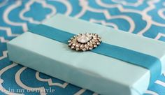 Pretty gift wrap and ribbon idea for small boxes. Use a piece of jewelry to embellish.