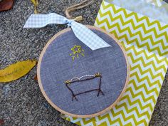 Sweet little hoop art on dark fabric, showing the manger with the star shining above.