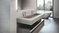 Trueform Concrete 60 ADA floating concrete sink in a contemporary bathroom.  Wall mount faucets and limestone walls.