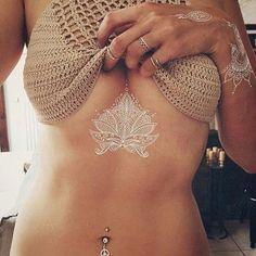 Tatuagem temporária branca que imita renda no meio dos seios