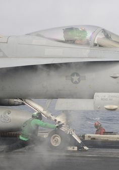 """GULF OF OMAN (Aug. 20, 2013) An aviation boatswain's mate (equipment) prepares an F/A-18C Hornet assigned to the """"Death Rattlers"""" of Marine Fighter Attack Squadron (VMFA) 323 for launch from the flight deck of the aircraft carrier USS Nimitz (CVN 68).  (U.S. Navy photo by Mass Communication Specialist 2nd Class Jacquelyn D. Childs/ Released)"""