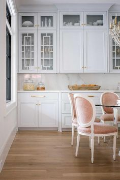 Light gray butler pantry features pink round back French dining chairs positioned around a round lucite dining table lit by a crystal beaded chandelier. French Dining Chairs, Round Back Dining Chairs, Dining Table Chairs, A Table, Dining Room, Room Chairs, Dining Area, Glass Shelving Unit, Ivory Kitchen