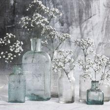 Mismatched bottles and jars - super cheap wedding decor. 5 Ways to Cut Wedding Decor Costs from www.daydreamingbride.com. #wedding, #weddingblog, #cheapwedding, #weddingflowers, #DIYwedding