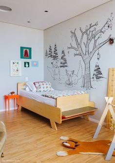 Quarto infantil tem móveis de madeira clara e desenho personalizado na parede.