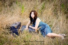 2014 High School Senior girl for posing picture ideas. Senior girl in a nature setting with vintage suitcases. High school senior session pose inspiration for senior pictures.