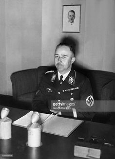 Heinrich Himmler, chief of the Gestapo, is shown seated at his office desk in Berlin. Photograph.