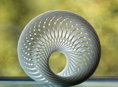 Mobius Nautilus is a 3D printed sculpture by Joaquin Baldwin. A compound mobius strip created out of 36 interlocking mobius strips. All segments are thin mobius strips, and they weave and interlock perfectly through the spaces left between them. Highly complex, and a headache to look at, yet it possesses an inherent mathematical simplicity and beauty.