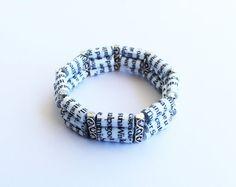 Eine gebildete Armband aus Papier-Perlen, die ich aus einem alten Buch in Handarbeit. Jedes Korn wird sorgfältig geschnitten, dann gerollt, geklebt, versiegelt mit einer Acryl-Lack und dann eine glänzende Deckfarbe. Die Perlen sind sehr winterhart, aber unglaublich leicht, machen dieses Armband angenehm zu tragen. Die Papier-Perlen sind ergänzt durch antikisiert Silber Perlen und aufgereiht auf klare elastische Schnur, die es vielseitig macht. Das Armband ist dreifach angeschwemmt und…