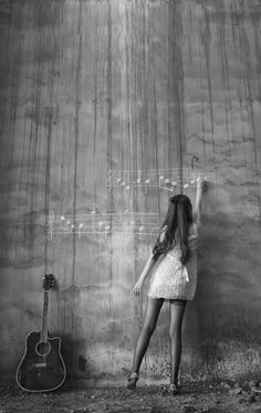 ♫♪ MUSIC ♪♫ is my soul Little girl writing music notes on the grey wall. Black & white image