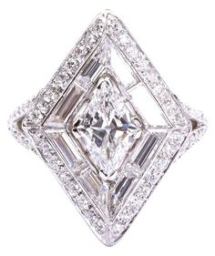 Art Deco Lozenge Diamond Ring. Centring a lozenge shaped brilliant-cut diamond weighing 1.10 carats, surrounded by 3.00 carats of calibré baguette and brilliant-cut diamonds, mounted in platinum.