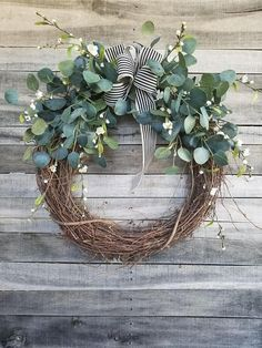This 26 Eucalyptus Wreath with a touch of little white flowers is the perfect simple accent for your door or interior. A wired black and cream ribbon makes a simple bow. FRONT DOOR WREATH. Love this wreath Average Diameter: 26 (tip to tip) This wreath will be created on a grapevine