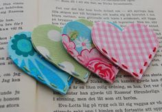 These are corner bookmarks using small scraps of fabric. Maybe use scrapbook paper? Monster's with googley eyes for boys!
