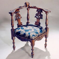 Baroque style elaborately carved walnut corner chair. With intricate detail, the chair splats with griffins; the arms and rail top with leaves and acorns and centred with a young cherub face carved into a shell; the apron with a swirl and leaf