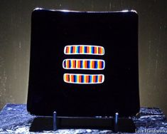 This is a (approximately 5 square slumped fused glass dish. It is a black plate with three multi-coloured strips in the centre of it. This piece is food safe. Each of my fused glass Bottle Slumping, Glass Beer Mugs, Getting Fired, Square Plates, Glass Dishes, Safe Food, Fused Glass, Liquor, Bubbles