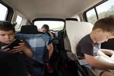 """Three boys entertain themselves with games and coloring in car on long trip. """"Are we there yet?"""" Find the best prices for your car parts at www.breakeryard.co.uk"""