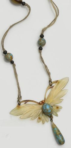 An Art Nouveau carved horn pendant, by Elizabeth Bonté. Designed as a butterfly, applied with a simulated turquoise paste bead, with similar drop, to a silk cord mounted with brown and blue glass beads, signed to the reverse. #ElizabethBonte #ArtNouveau #pendant