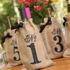 Here's a cool idea - a bottle of wine for each table, with numbered burlap bags over each!